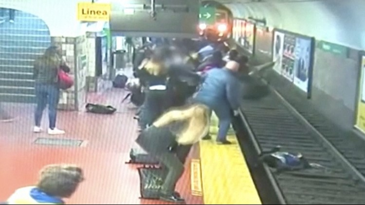 Watch passengers stop subway train from hitting woman who fell on tracks